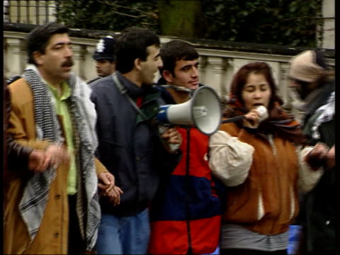 london greek embassy ext kurdish demonstrator waving flag as others dance behind ms kurdish demonstrators dancing as one singing into loudhailer ms... - charing cross stock videos and b-roll footage
