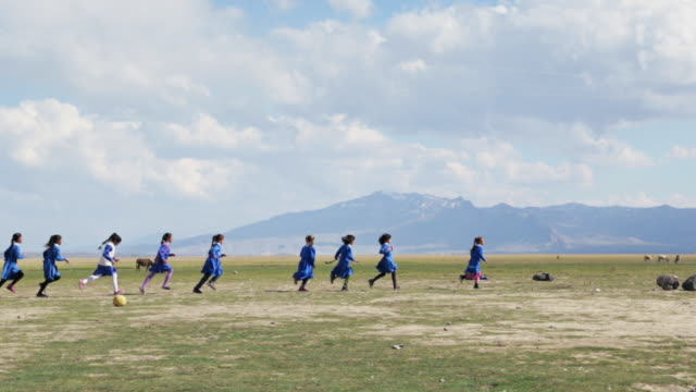 Kurdish school kids running on wide field in Eastern Anatolia.