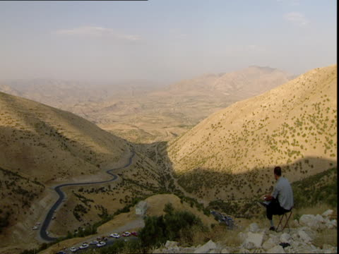 kurdistan mountain pass man sitting on folding chair and looking at winding road with cars in valley / kurdistan iraq - winding road stock videos & royalty-free footage