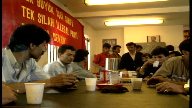 40 kurds sitting around in housing refugee making london 'v' sign piles of clothes and suitcases kurds seated at table exterior 0537 exterior 'union... - kurdischer abstammung stock-videos und b-roll-filmmaterial