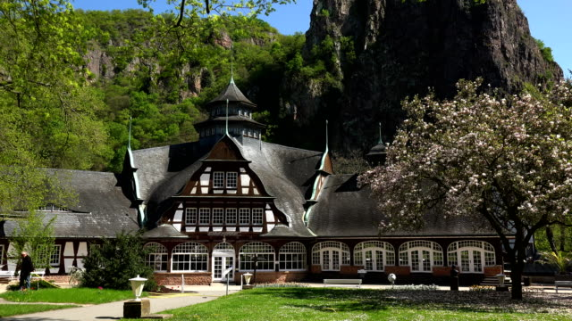 kurhaus building with rheingrafenstein rock formation in bad muenster am stein, nahe valley, rhineland-palatinate, germany - thatched roof stock videos and b-roll footage