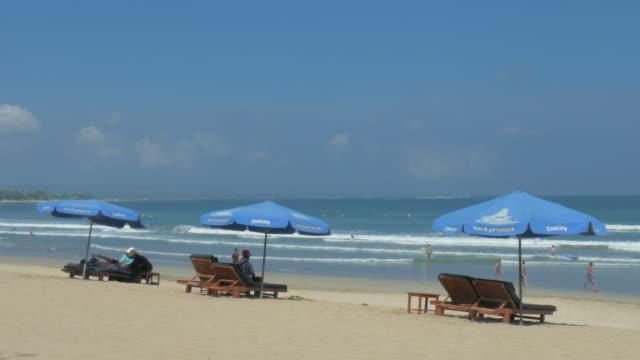 vídeos de stock e filmes b-roll de kuta beach,kuta,bali,indonesia - chapéu de sol