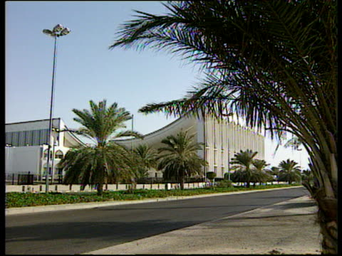 kuwait national assembly building zoom to side of building near roads and palm trees - kuwait stock videos and b-roll footage