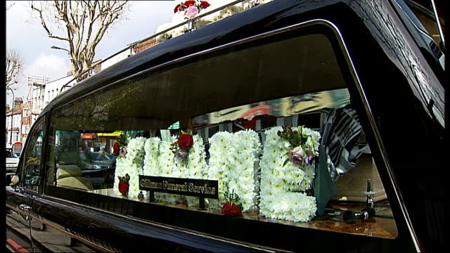 funeral service held england london dulwich ext floral tibute spelling out kwame in hearse with coffin coffin being carried into church and people... - carro funebre video stock e b–roll