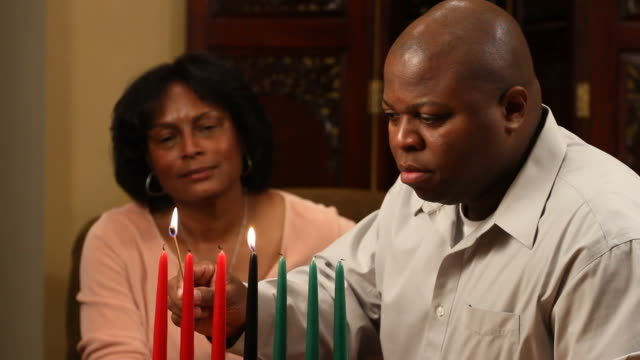 Kwanzaa Couple Man Lights Candles