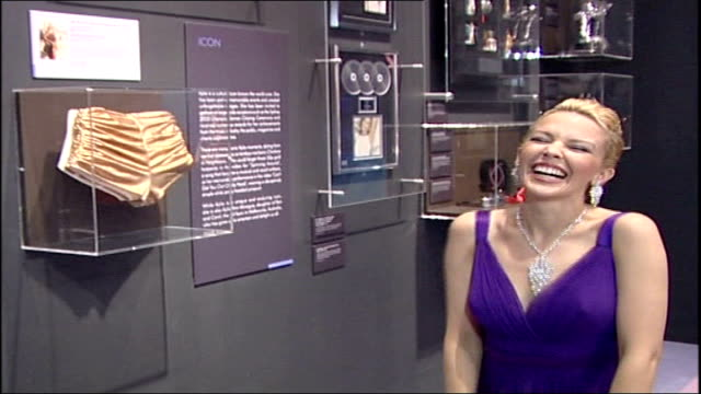 kylie minogue clothes exhibition at the victoria & albert museum; int minogue examining gold pants in glass case minogue and baker visiting... - kylie minogue the exhibition stock videos & royalty-free footage