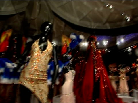 kylie minogue clothes exhibition at the victoria & albert museum; glitterball on ceiling dresses on mannequins in kylie exhibition gold bra and skirt... - kylie minogue the exhibition stock videos & royalty-free footage