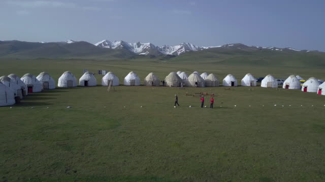 vídeos de stock, filmes e b-roll de kyrgyzstan, tian shan mountains, aerial view of yurt camp near the song kul high alpine lake - equipamento doméstico