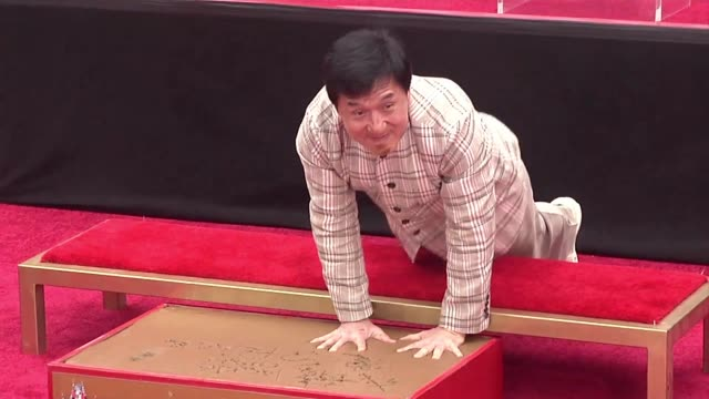 vídeos de stock e filmes b-roll de la estrella del kung fu jackie chan se convirtio el jueves en el primer actor chino en dejar sus huellas en el cemento del teatro chino de hollywod... - jackie chan