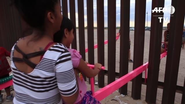 vídeos y material grabado en eventos de stock de la frontera entre mexico y estados unidos se convirtio en un parque de juegos con la instalaciones de tres balancines conocidos como sube y baja como... - ee.uu