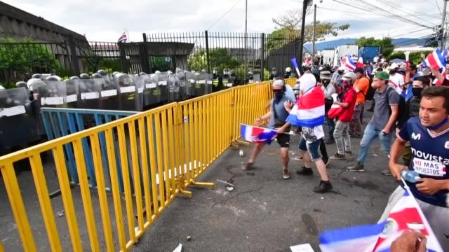 vídeos y material grabado en eventos de stock de la policía de costa rica usó gases lacrimógenos para dispersar a manifestantes que embistieron y lanzaron piedras a los agentes, tras una marcha... - llevar