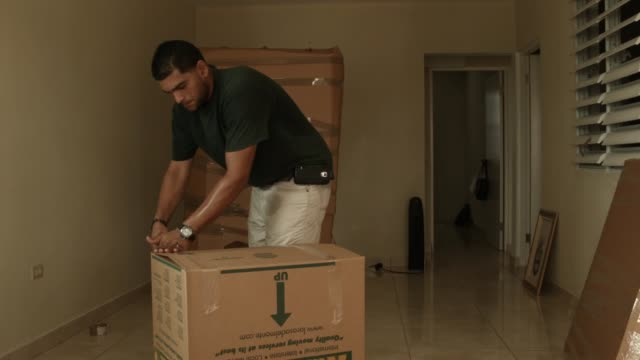 la rosa del monte movers pack up yessenia puente's apartment as she prepares to move to orlando, florida this weekend on july 1, 2015 in san juan,... - puente点の映像素材/bロール