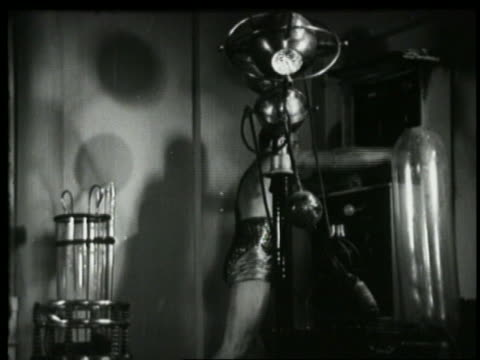 B/W 1935 lab assistant in glittery underwear pushing levers