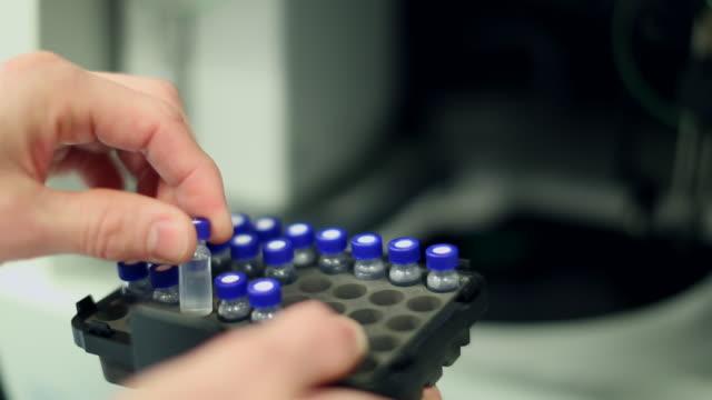 vídeos de stock, filmes e b-roll de lab technician handling a block of vials - amostra científica