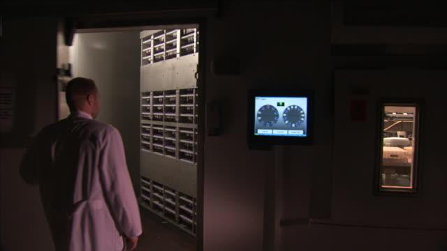 a lab technician looks into a walk-in refrigerator full of racks. - 保管場所点の映像素材/bロール