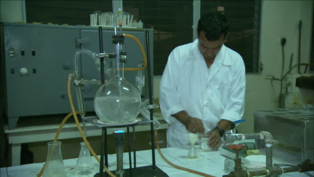 a lab technician pours a chemical into a small container. - reifenschlauch stock-videos und b-roll-filmmaterial