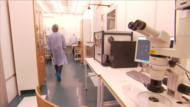 a lab technician steps away from a microscope to a computer. - optisches gerät stock-videos und b-roll-filmmaterial
