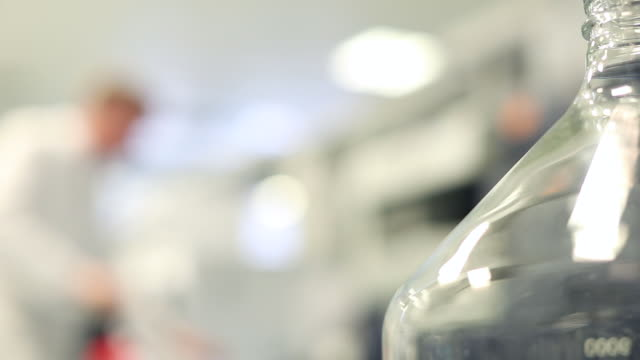Lab Technician Working behind a Glass Beaker in a Laboratory