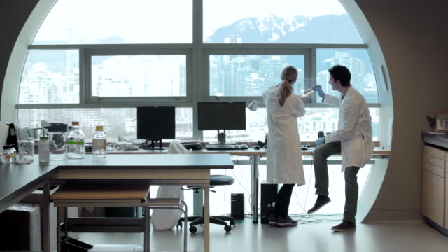 MS PAN Lab technicians discussing DNA gels at window Vancouver mountains in Cancer research Healthcare medicine Industry DNA sequencing Laboratory / Vancouver, BC, Canada