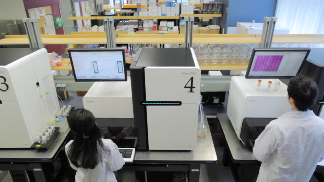 ms pov lab technicians working on hiseq2000s dna sequencers / vancouver, bc, canada - medical test stock videos & royalty-free footage
