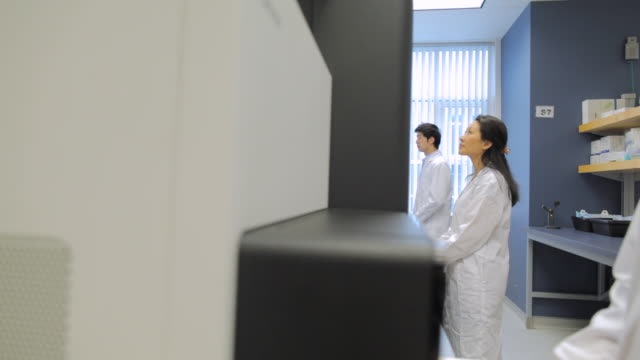 MS POV Lab technicians working on HiSeq2000s DNA sequencers / Vancouver, BC, Canada