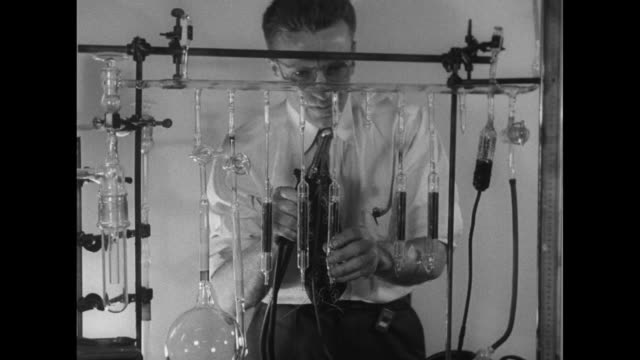 Lab worker stands behind array of glass tubing and heats ampule with small torch / dark liquid drips into cylindrical glass container / liquid is...
