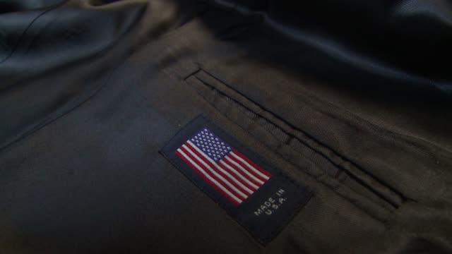 a label is sewn on the pocket of a pair of trousers. available in hd. - hosentasche stock-videos und b-roll-filmmaterial