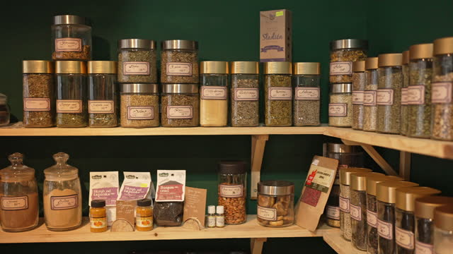 labeled jars of different dried tea on the shelf at the modern health food store shop - natural condition stock videos & royalty-free footage