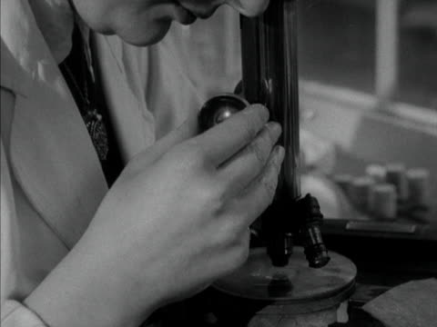 a laboratory assistant adjusts a microscope 1958 - microscope stock videos & royalty-free footage