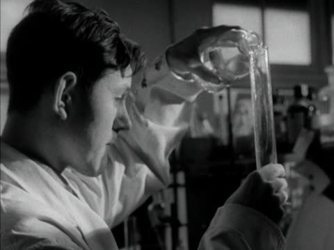 a laboratory assistant pours a liquid into a large glass phial 1958 - laboratory equipment stock videos & royalty-free footage