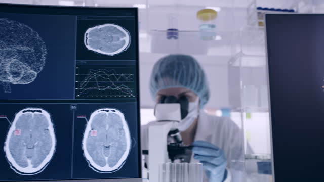 laboratory equipment. brainwave research on screens. female scientist working with microscope in background - human nervous system stock videos & royalty-free footage