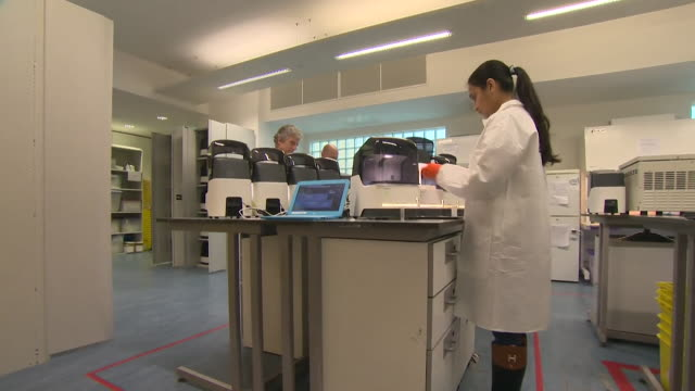 laboratory staff carrying out coronavirus tests on a samba 2 machine that they are trialling at addenbrookes hospital, that can give a test result in... - scientific experiment stock videos & royalty-free footage