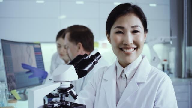 laborteam, das mit krankheitserregerproben arbeitet. asiatische ärztin lächelnd in eine kamera - vergrößerung stock-videos und b-roll-filmmaterial