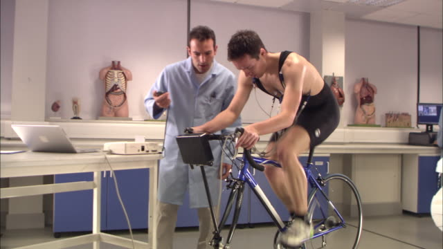 ws, laboratory worker supervising man riding stationary bicycle, london, england - scrutiny stock videos & royalty-free footage