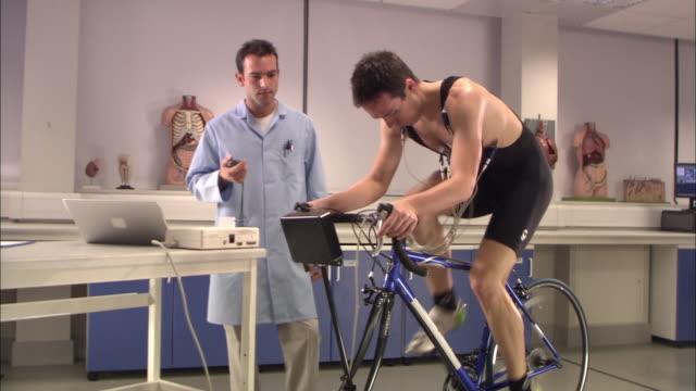 zo, ws, laboratory worker supervising man riding stationary bicycle, london, england - エアロバイク点の映像素材/bロール