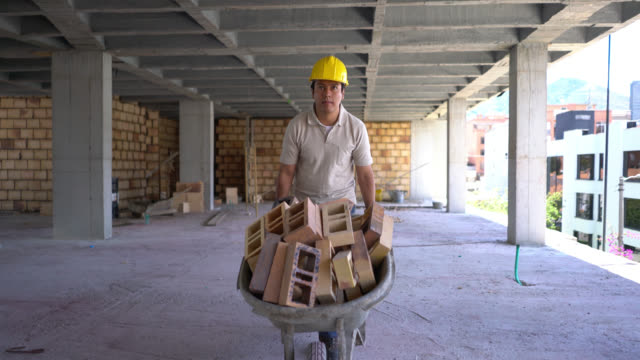 laborer at a construction site moving a wheelbarrow full of bricks to another place - wheelbarrow stock videos and b-roll footage