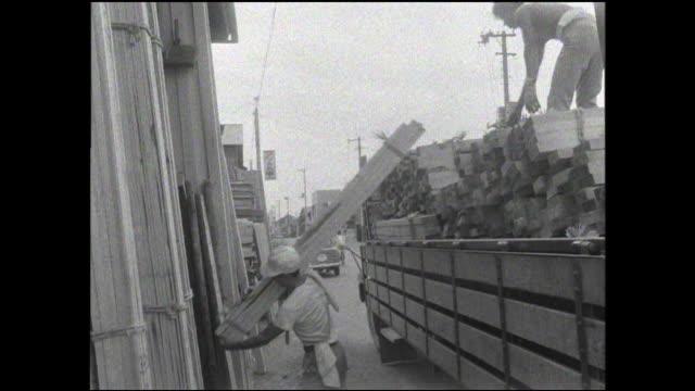 vidéos et rushes de a laborer carries a plank into a lumberyard warehouse. - planche de bois