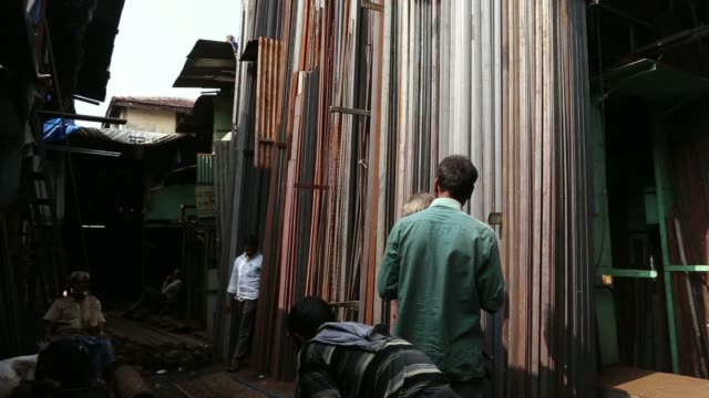 vidéos et rushes de a laborer takes out and cut steel rods at a steel rod shop in mumbai india on thursday dec 5 a laborer cuts a steel plank with torch - tôle