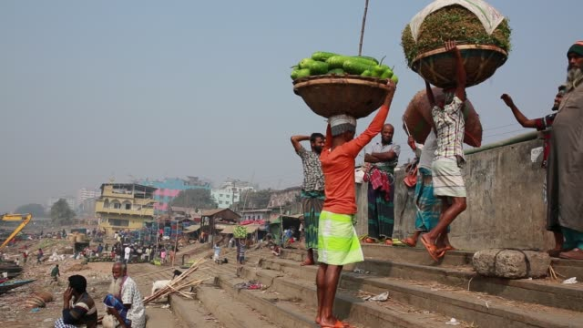 Laborer unloading crops from boat at a temporary wholesale market at the bank of the Buriganga River in Dhaka Bangladesh on March 19 2018 The...