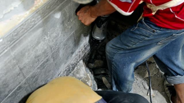 laborer using electric jackhammer with drilling ground of renovation - attrezzi da lavoro video stock e b–roll