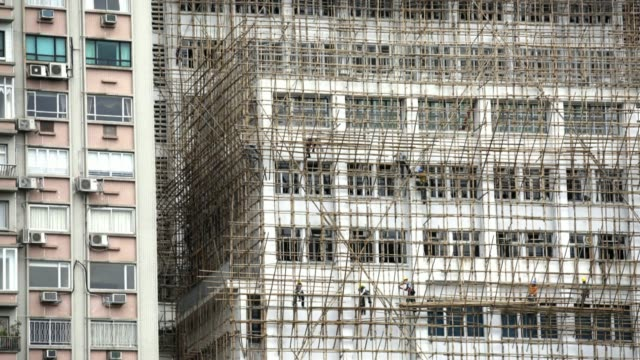 stockvideo's en b-roll-footage met laborers construct bamboo scaffolding around a building in the sheung wan district of hong kong on saturday april 26 2014 - hongkong eiland