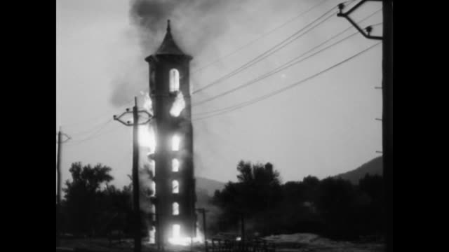 / laborers take hammers to old mill tower erected in 1853 by samuel williston / knock down bricks and make fire at base / set fire to tower / burns... - 1932 stock videos and b-roll footage