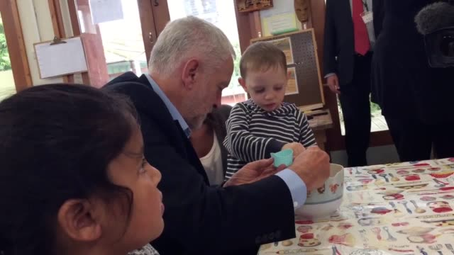 labour leader jeremy corbyn is greeted by bagpipes at a sure start centre in corby northamptonshire he bakes cakes with the children at the centre - northamptonshire stock videos and b-roll footage