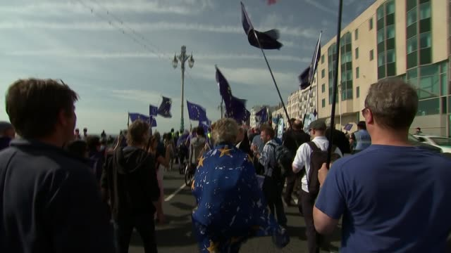 vídeos de stock e filmes b-roll de divisions over brexit england east sussex brighton ext gvs antibrexit protesters marching on seafront with eu flags and chanting 'exit brexit' sot... - east sussex