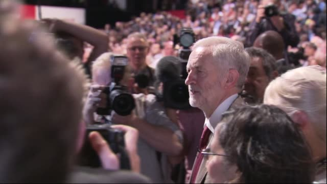 jeremy corbyn speech **music heard sot** corbyn along leaving stage and hugging people in audience corbyn surrounded by press and waving to audience - umgeben stock-videos und b-roll-filmmaterial