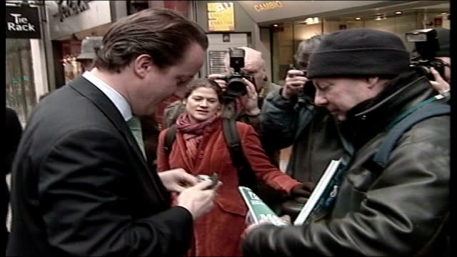 Labour Party funding crisis TX David Cameron MP buying a 'Big Issue' magazine from a vendor DISSOLVE TO