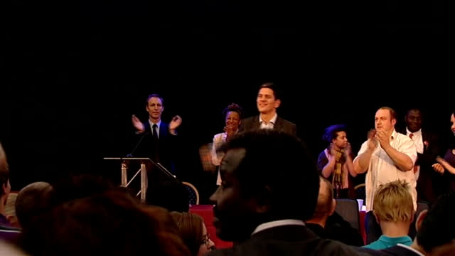 david miliband speech **music heard sot** wide shot of miliband on stage during standing ovation / miliband waving and giving thumbs up sign - david miliband stock videos & royalty-free footage