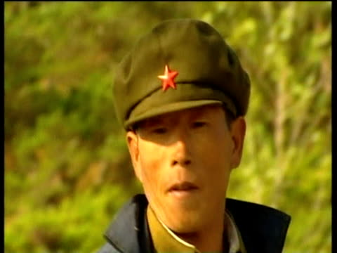 labourer in communist cap uses fork to place loads of hay onto truck north korea; 2005 - 干草用熊手点の映像素材/bロール