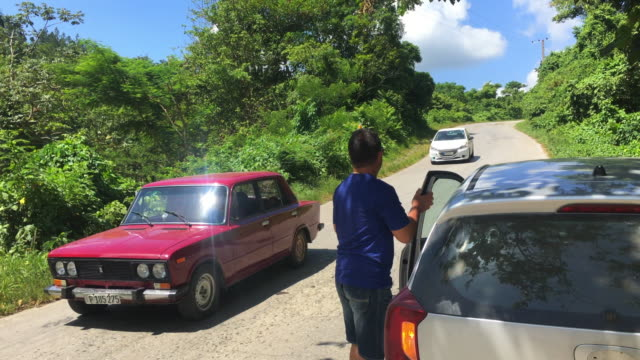 a lada auto and a small rental car drive in the dirt road 'topes de collantes' in the cuban province of sancti spiritus is a major ecotourism... - sancti spiritus province stock videos and b-roll footage