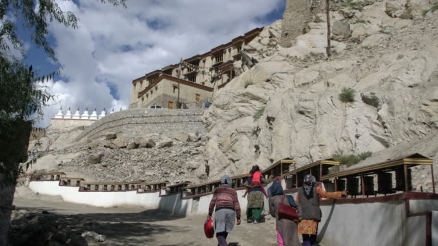ladakhi women spinning prayer wheels in front of the shey palace complex in ladakh, india - monastery stock videos & royalty-free footage